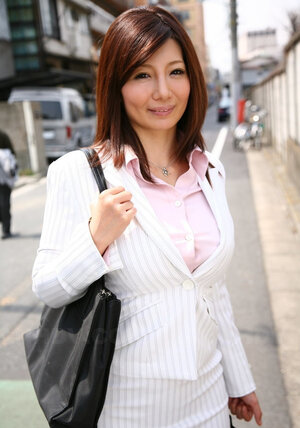 Successful Japanese businesswoman in the sexy snow-white suit on the way to work