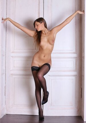 Beautiful immature woman poses in front of big doors hiding nothing under her clothes