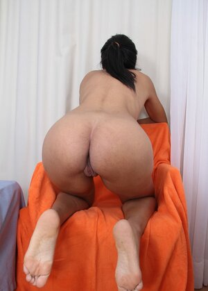 Sexy black chick gets on an armchair to expose her private body fragments